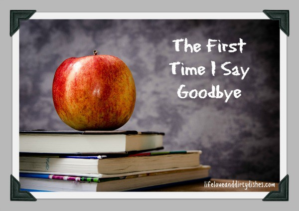 Apple on some books in front of a chalk board. The First Time I say Goodbye is written on the chalk board. for my son's first day at school