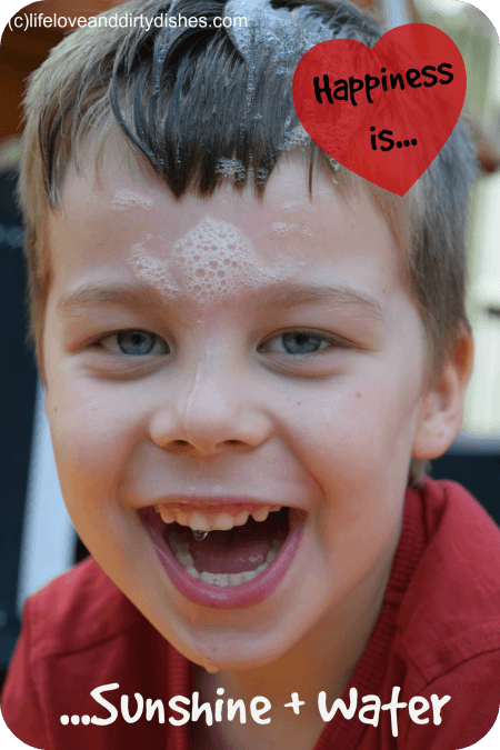 Image of boy playing in the garden soaked with water laughing and happy