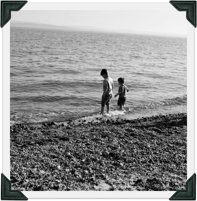Image of two boys paddling in the sea