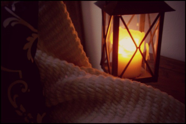 Image of a warm blanket and a lantern depicting a cosy winter night in