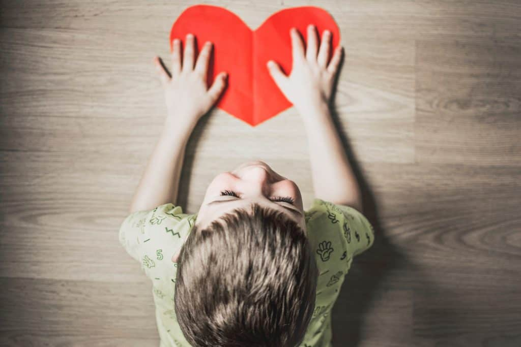 child led on floor with a red paper heart