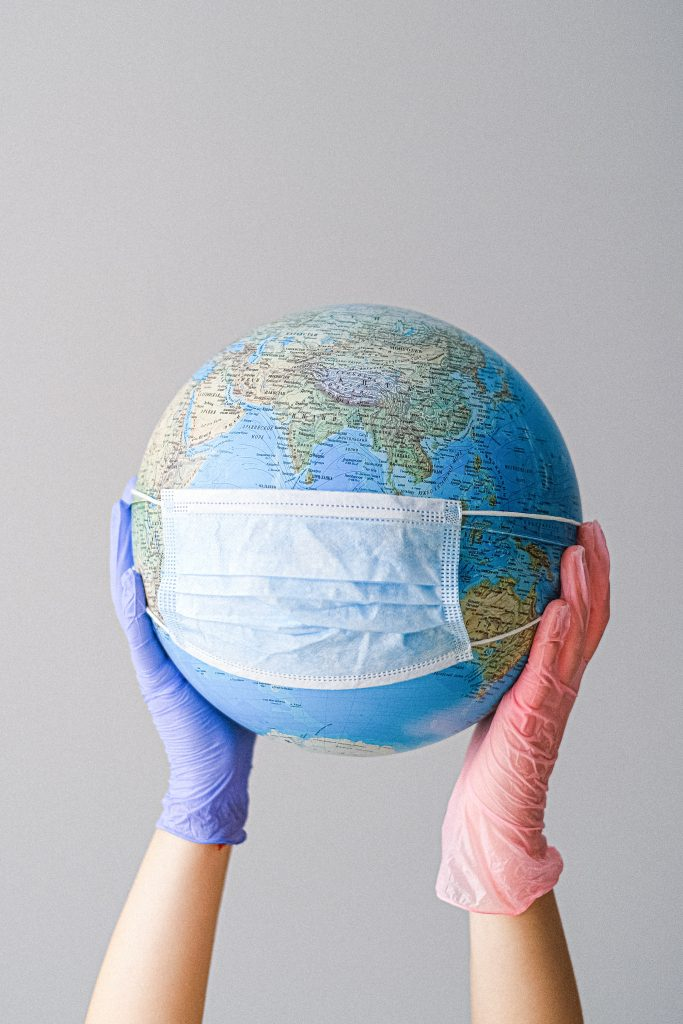 A globe with a face mask on.  The benefits of wearing a face mask